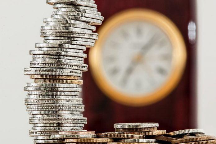 monede si un ceas, timpul costa bani