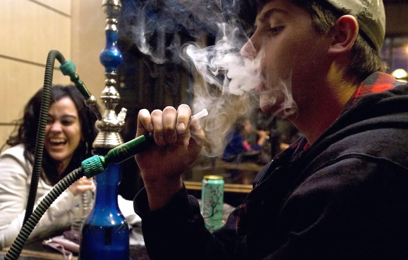 Prieteni pe terasă care fumează narghilea