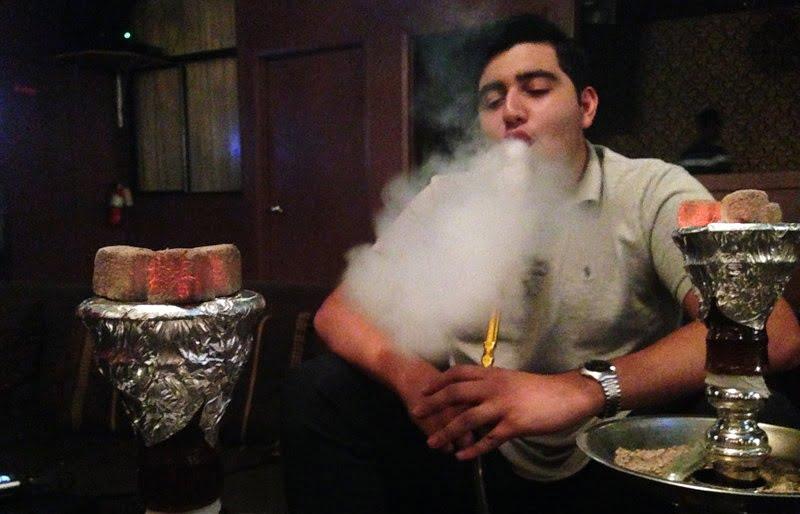 Băiat care scoate fum de narghilea la restaurant